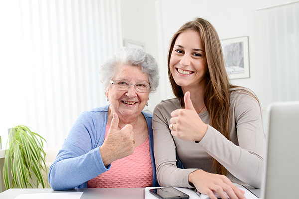 mother and daughter using computer with thumbs up